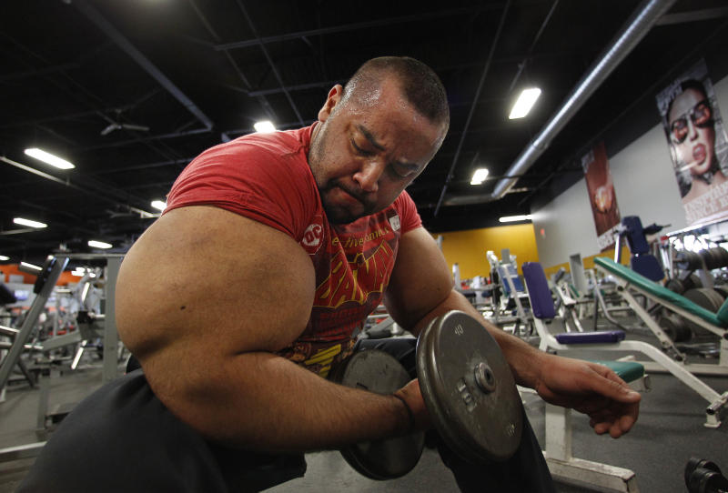 In this photo taken, Friday, Nov. 16, 2012, Egyptian Body builder Moustafa Ismail lifts free weights during his daily workout at World Gym in Milford, Mass. Ismail has been given the title of world's biggest arms, biceps and triceps, by the Guinness Book of World Records. (AP Photo/Stephan Savoia)
