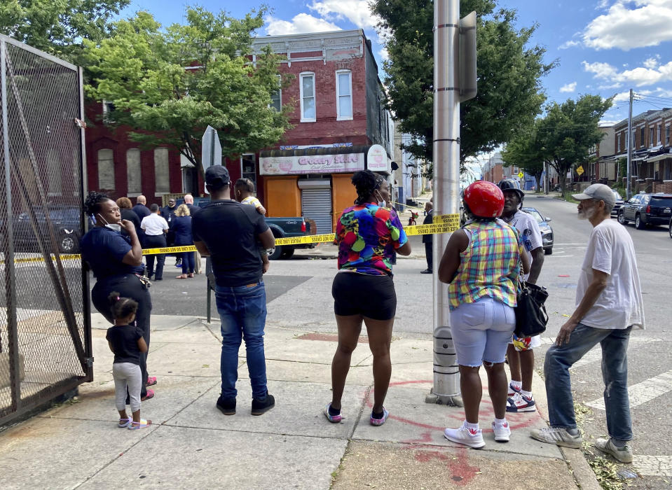A cluster of people watch as Baltimore Police investigate a shooting, Wednesday, June 16, 2021, in Baltimore. One person was killed and five others were wounded Wednesday when gunmen walked up a street and opened fire on a Baltimore block from an intersection, the city's police commissioner said. (Kim Hairston/The Baltimore Sun via AP)