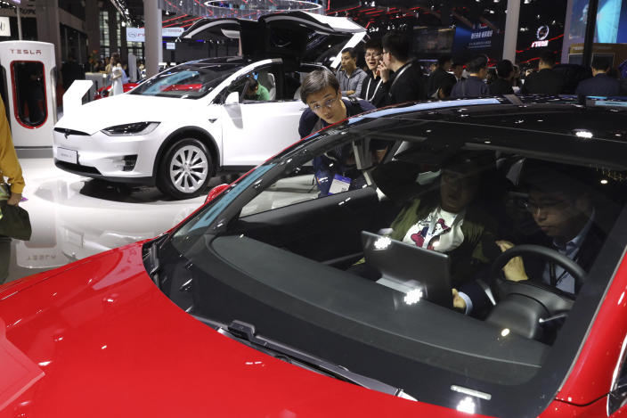 In this April 17, 2019, photo, attendees take a look at electric cars from Tesla at the Auto Shanghai 2019 show in Shanghai. China's electric car sales are stalling following the end of multibillion-dollar subsidies that made it the biggest market for the technology. Communist leaders want to make China a leader in electric cars but are shifting the burden to the industry by imposing mandatory sales quotas. (AP Photo/Ng Han Guan)