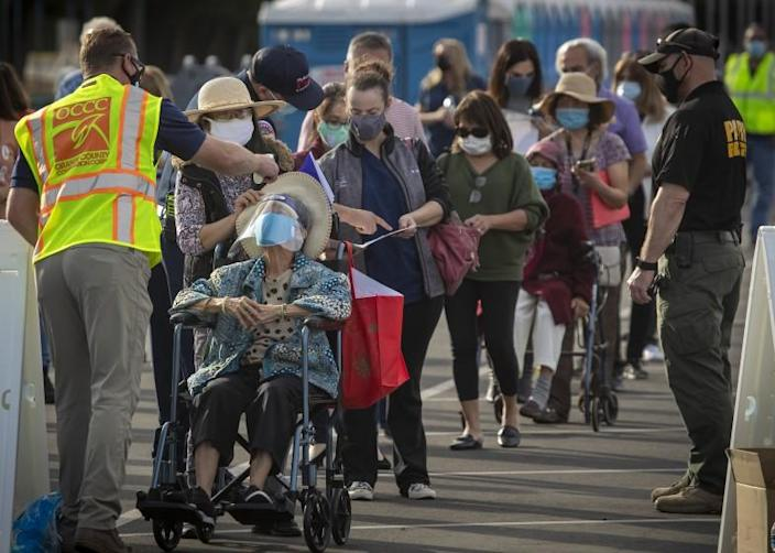 Anaheim, CA - January 13: Officials take the temperature of Orange County active Phase 1A (critical and healthcare workers) residents as they line up to enter large tents at Orange County's first large-scale vaccination site to receive the Moderna COVID-19 vaccine in the Toy Story parking lot at the Disneyland Resort in Anaheim Wednesday, Jan. 13, 2021. Orange County supervisors and Orange County Health Care Agency Director Dr. Clayton Chau held a news conference discussing the county's first Super POD (point-of-dispensing) site for COVID-19 vaccine distribution. The vaccinations are at Tier 1A for people who have reservations on a website. The site is able to handle 7,000 immunizations per day. Their goal is to immunize everyone in Orange County who chooses to do so by July 4th. (Allen J. Schaben / Los Angeles Times)