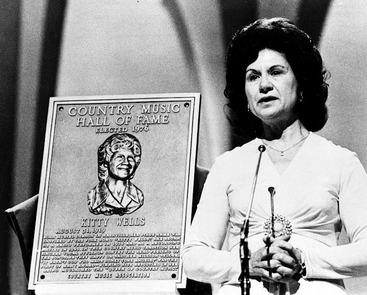 """FILE - This 1976 file photo shows Country Music Hall of Fame inductee Kitty Wells during the Country Music Association (CMA) awards in Nashville, Tenn. Wells, the first female superstar of country music, has died at the age of 92. The singer's family says Wells died at her home Monday after complications from a stroke. Her recording of """"It Wasn't God Who Made Honky Tonk Angels"""" in 1952 was the first No. 1 hit by a woman soloist on the country music charts. Other hits included """"Making Believe"""" and a version of """"I Can't Stop Loving You."""" (AP Photo, file)"""