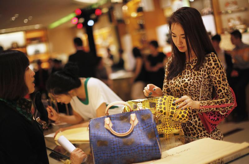 A woman shops in Louis Vuitton store during Vogue's 4th Fashion's Night Out: Shopping Night with Celebrities in downtown Shanghai