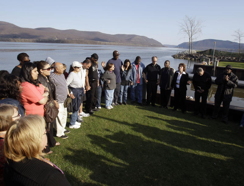 FILE - In this Thursday, April 14, 2011 file photo, people attend a vigil at the boat ramp where Lashanda Armstrong drove her minivan into the Hudson River on Tuesday night killing herself and three of her children, in Newburgh, N.Y. Mothers kill their children in this country much more often than most people would realize by simply reading the headlines; by conservative estimates it happens every few days, at least 100 times a year. Experts say more mothers kill their children under 5 years of age than fathers. And, some say, our reluctance as a society to believe mothers would be capable of killing their offspring is hindering our ability to recognize warning signs, intervene and prevent more tragedies. (AP Photo/Mike Groll, File)