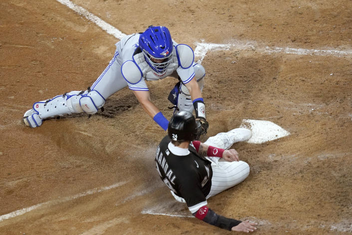 Toronto Blue Jays catcher Reese McGuire tags out Chicago White Sox's Yasmani Grandal at home during the fourth inning of a baseball game Wednesday, June 9, 2021, in Chicago. (AP Photo/Charles Rex Arbogast)