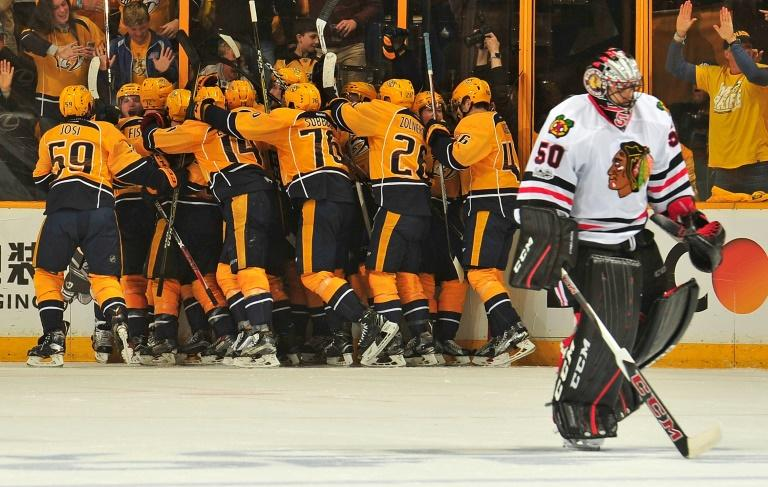 Kevin Fiala is swarmed by Nashville Predators  teammates after scoring the game-winning overtime goal against the Chicago Blackhawks