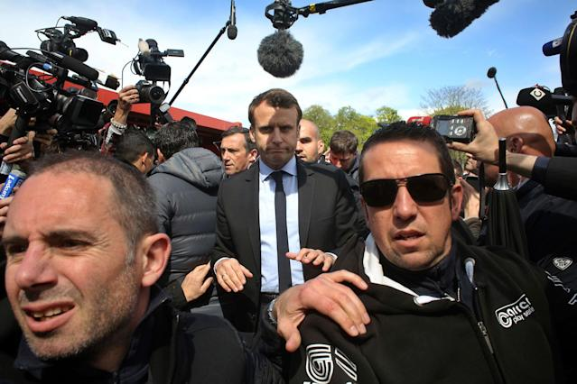 <p>French centrist presidential election candidate Emmanuel Macron, center, makes his way at the Whirlpool home appliance factory, Wednesday April 26, 2017 in Amiens, northern France. Far-right French presidential candidate Marine Le Pen has earlier upstaged Macron as she made a surprise campaign stop to the plant. (AP Photo/Thibault Camus) </p>