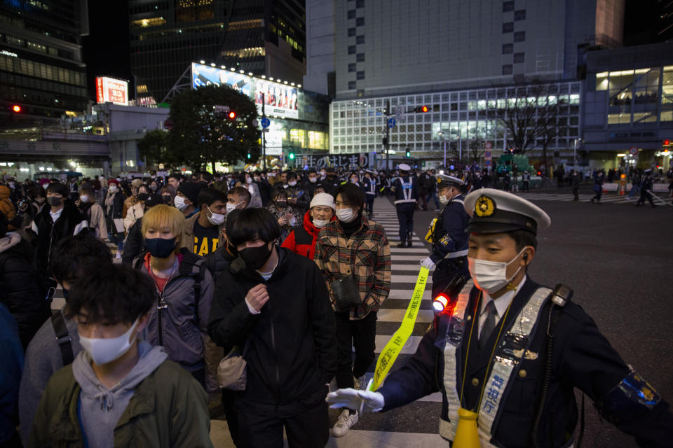 """Police direct visitors around Shibuya crossing, a popular location for New Year's Eve gathering Friday, Jan. 1, 2021, in Tokyo. Tokyo's downtown Shibuya district has canceled its annual countdown event at a popular """"scramble Intersection"""" area outside of its main train station, and a """"countdown vision"""" screen will be turned off at 11 p.m. (AP Photo/Kiichiro Sato)"""