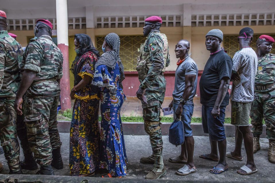 Civilians and soldiers line up to vote at the Boulbinet Deaf School in Conakry, Guinea, Sunday Oct. 18, 2020. Guinean President Alpha Conde is seeking to extend his decade in power, facing off against his longtime rival Cellou Dalein Diallo for the third time at the polls. (AP Photo/Sadak Souici)
