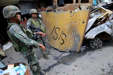 FILE PHOTO: Government soldiers stand on guard in front of damaged buildings as troops continue their assault on its 105th day of clearing operations against pro-IS militants who have seized control of large parts of Marawi City, Philippines September 4, 2017. REUTERS/Romeo Ranoco