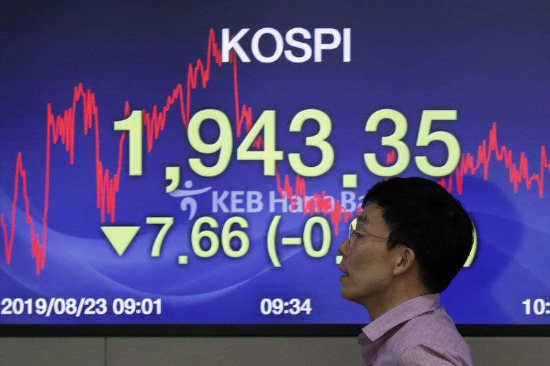 A currency trader walks by the screen showing the Korea Composite Stock Price Index (KOSPI) at the foreign exchange dealing room in Seoul, South Korea, Friday, Aug. 23, 2019. Asian stock markets were mixed on Friday after Wall Street declined ahead of a closely watched speech by the U.S. Federal Reserve chairman. (AP Photo/Lee Jin-man)