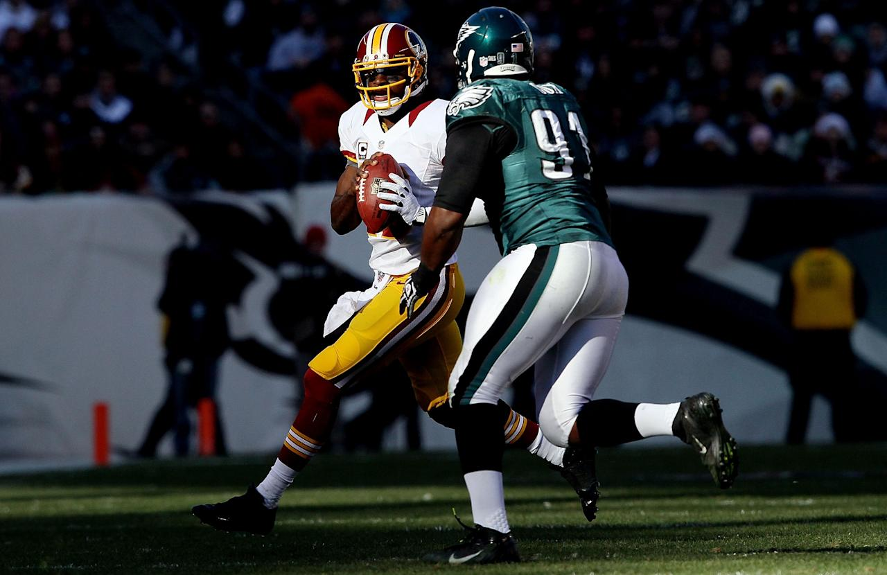 PHILADELPHIA, PA - DECEMBER 23: Robert Griffin III #10 of the Washington Redskins looks to make a pass as Fletcher Cox #91 of the Philadelphia Eagles defends at Lincoln Financial Field on December 23, 2012 in Philadelphia, Pennsylvania.  (Photo by Alex Trautwig/Getty Images)