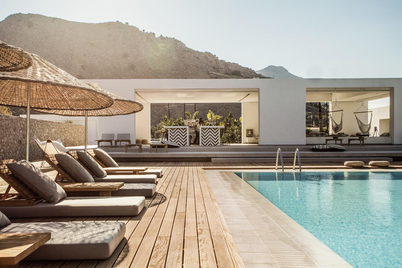 """Nomadic style meets traditional Greek architecture at <a rel=""""nofollow"""" href=""""https://casacook.com/"""">Casa Cook</a>, a 90-room, 16+ hotel located in Kolympia, on the island's northeast side. Common spaces accent exposed stone walls and tables, and feature wooden decks, jute rugs, hammocks, and pergolas; rooms have low-slung furniture, pendant lighting, wire chairs, straw poufs, and linen and rough cotton furnishings that contribute to the resort's all-around bohemian vibe."""