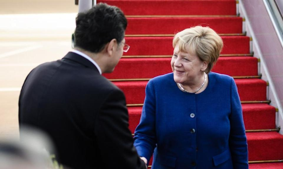 Qin Gang, then vice-minister for foreign affairs, greets Angela Merkel on arrival in China in 2018