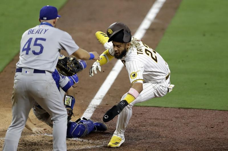 San Diego Padres' Fernando Tatis Jr., right, is tagged out by Los Angeles Dodgers catcher Will Smith, behind center, attempting to score from third off a line out by Manny Machado as Los Angeles Dodgers first baseman Matt Beaty (45) looks on, left, during the seventh inning of a baseball game Monday, Aug. 3, 2020, in San Diego. (AP Photo/Gregory Bull)