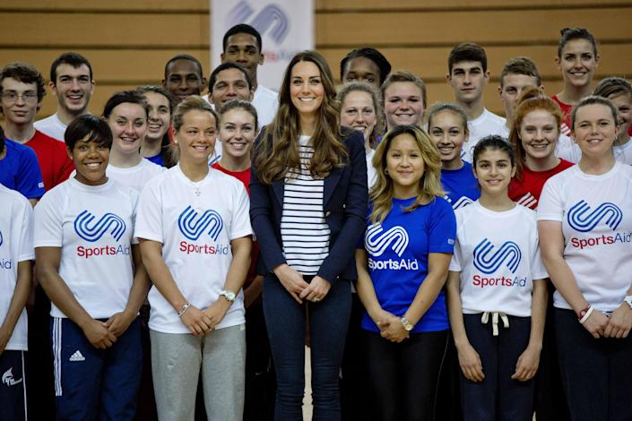Britain's Catherine, Duchess of Cambridge (C) poses with young athletes for a group photograph as she attends a SportsAid athlete workshop at the Copper Box in the Olympic Park in London October 18, 2013. REUTERS/David Bebber/Pool (BRITAIN - Tags: ROYALS ENTERTAINMENT SPORT)