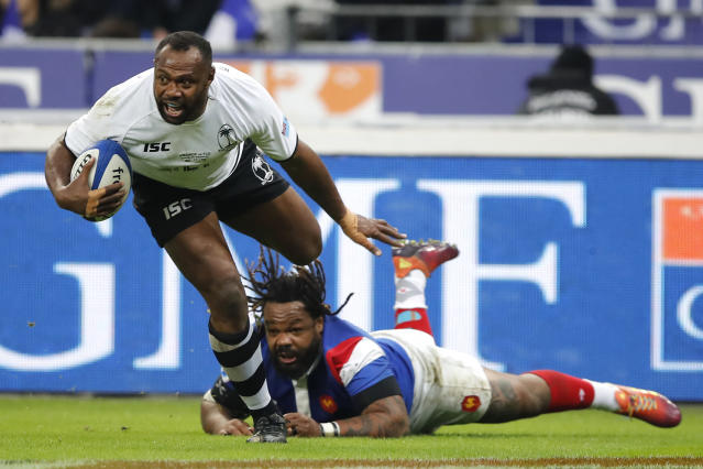 FILE - In this Nov. 24, 2018, file photo, Fiji's Vereniki Goneva evades the tackle of France's Mathieu Bastareaud as he scores a try that was disallowed on video review during the rugby international between France and Fiji at Stade de France in Paris. The powerful Fiji wing and center who will be playing at his third World Cup, Goneva became his nation's leading test try-scorer this season and remains one of the world's most sought-after players at 35. (AP Photo/Christophe Ena, File)