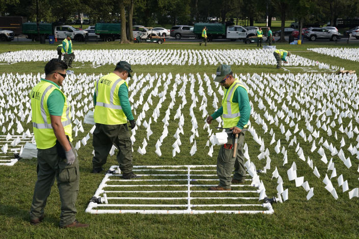 """Workers plant white flags as part of artist Suzanne Brennan Firstenberg's temporary art installation, """"In America: Remember,"""" in remembrance of Americans who have died of COVID-19, on the National Mall in Washington, Tuesday, Sept. 14, 2021. The installation will consist of more than 630,000 flags when completed. (AP Photo/Patrick Semansky)"""