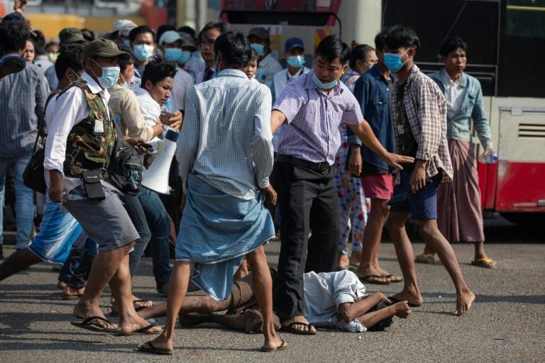 Military supporters stand over a man who was attacked during a rally in Yangon on Thursday