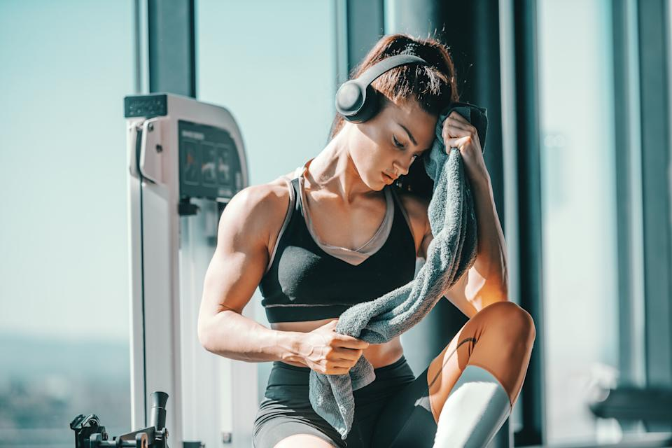 Serious muscular strong female bodybuilder with ponytail and headphones wiping sweat while sitting in gym next to window. The start is what stops most people.