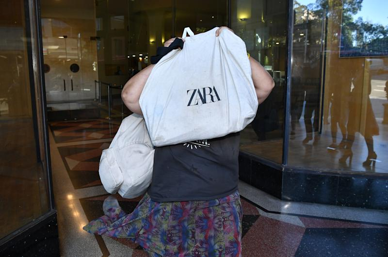 Elena Bobolas holds a bag over her face as she leaves the Downing Centre Local Court in Sydney on Tuesday. Source: AAP Image.