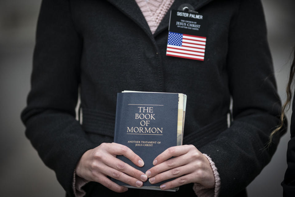 Sister Palmer, 19, holds The Book of Mormon while walking around Temple Square in Salt Lake City, Sunday, Nov. 15, 2020. Palmer, a member of The Church of Jesus Christ of Latter-day Saints, is serving an 18-month mission in Salt Lake City while waiting for her visa to continue the mission in Spain. (AP Photo/Wong Maye-E)