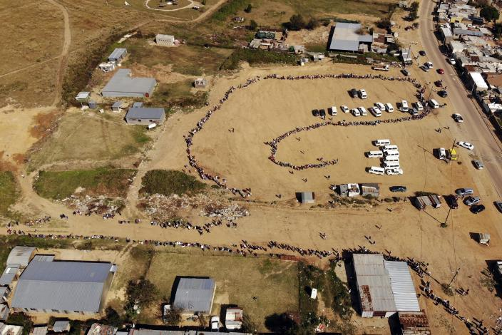 FILE — In this May 2, 2020 file photo thousands line up to receive food handouts in the Olievenhoutbos township of Midrand, South Africa. (AP Photo/Jerome Delay, File)