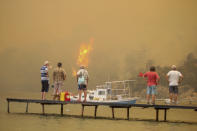 Tourists wait to be evacuated from smoke-engulfed Mazi area as wildfires rolled down the hill toward the seashore, in Bodrum, Mugla, Turkey, Sunday, Aug. 1, 2021. More than 100 wildfires have been brought under control in Turkey, according to officials. The forestry minister tweeted that five fires are continuing in the tourist destinations of Antalya and Mugla. (AP Photo/Emre Tazegul)
