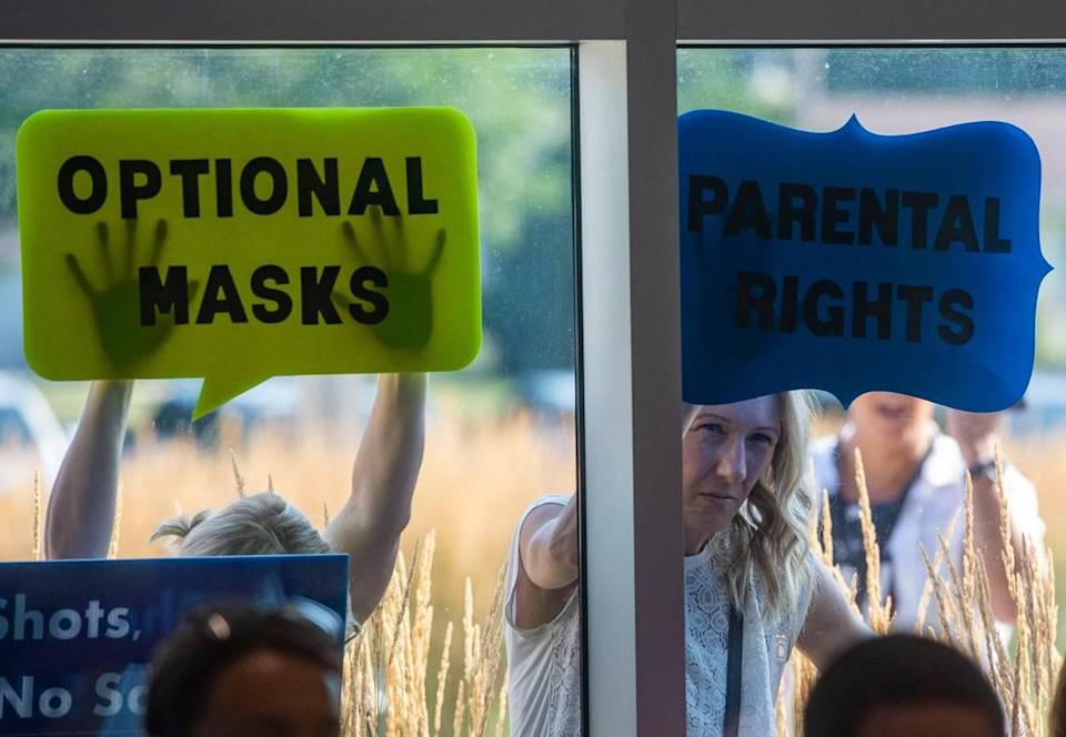 People stand with signs outside the Shawnee Mission School District board meeting Monday, listening on their phones as parents speak about their preferences for students wearing masks in the 2021-22 school year.