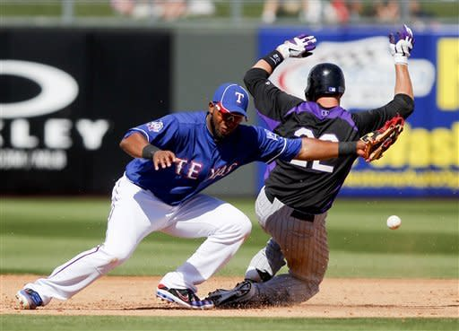 Texas Rangers shortstop Elvis Andrus, left, cannot reach a wild throw as Colorado Rockies' Jordan Pacheco slides safely into second after driving in two runs with a single and advancing to second on a throw home in the fifth inning of a spring training baseball game on Wednesday, March 14, 2012, in Surprise, Ariz. (AP Photo/Lenny Ignelzi)