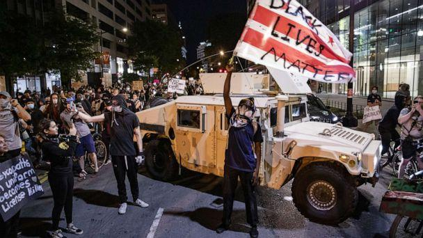 PHOTO: A protester waves a D.C. flag with Black Lives Matter spray painted on it next to a DC National Guard Humvee as people march through the streets during a demonstration over the death of George Floyd, June 2, 2020, in Washington, D.C. (Samuel Corum/Getty Images)