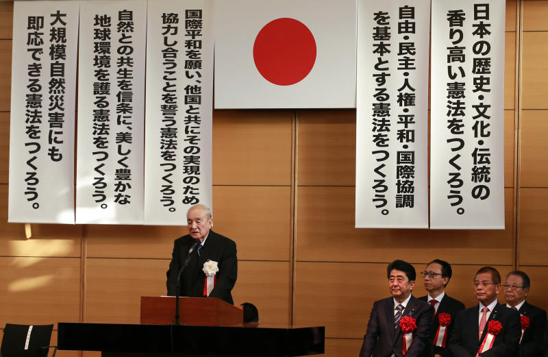 FILE- In this May 1, 2017 file photo, former Japanese Prime Minister Yasuhiro Nakasone makes a speech as Japanese Prime Minister Shinzo Abe, seated left, listens to him during the annual rally on revising Japan's constitution organized by ruling party lawmakers in Tokyo. One of Japan's most prominent former leaders, Nakasone has turned 100 years of age, fitting in a country known for longevity Nakasone, born on May 27, 1918, turns 100 on Sunday, May 27. (AP Photo/Shizuo Kambayashi, File)