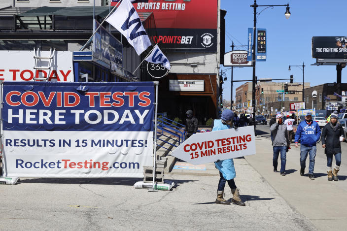 A person stands with a sign related to COVID-19 testing as Chicago Cubs fans pass by outside of Wrigley Field on the opening day baseball game between the Chicago Cubs and the Pittsburgh Pirates, Thursday, April 1, 2021 at Chicago. Fans are back at the ballpark after they were shut out during the regular season last year because of the coronavirus pandemic. (AP Photo/Shafkat Anowar)