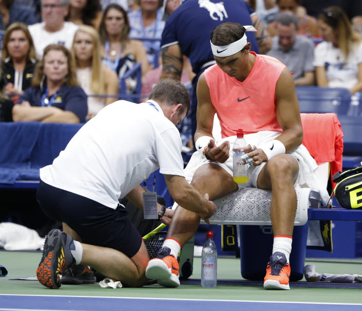 Rafael Nadal, of Spain, is seen by a trainer during the third round of the U.S. Open tennis tournament against Karen Khachanov, of Russia, Friday, Aug. 31, 2018, in New York. (AP Photo/Jason DeCrow)