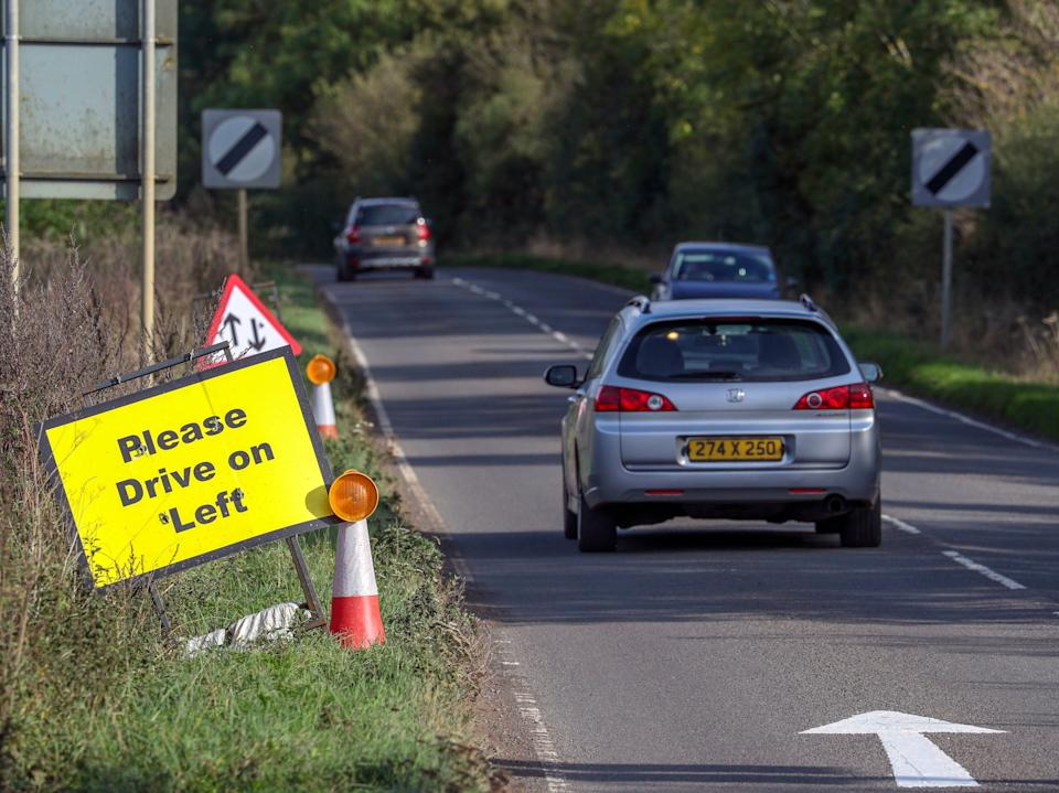 A vehicle with diplomatic plates passes a Please Drive on Left sign and road marking that have been placed on the B4031 outside RAF Croughton, where Harry Dunn diedPA