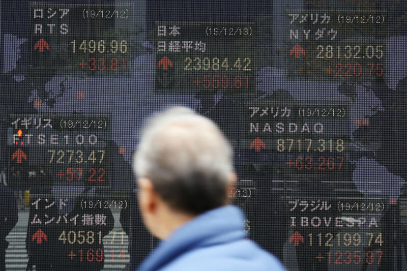 """A man looks at an electronic stock board showing Japan's Nikkei 225 index and other country's index at a securities firm in Tokyo. A closely watched economic survey by the Bank of Japan showed sentiments among major manufacturers soured for the fourth straight quarter, the """"tankan"""" survey released Friday, Dec. 13, 2019. A trade war between the U.S. and China crimped trade and growth. Japan's growth is dependent on exports and any slowdown in pan-Pacific trade hurts company sentiments. (AP Photo/Eugene Hoshiko)"""