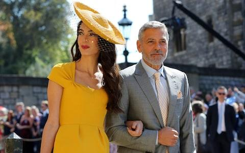 Clooney (pictured here with wife Amal at the wedding of Prince Harry and Meghan Markle earlier this year), has been in Sardinia for several weeks filming a TV remake of the novel Catch-22 - Credit: Gareth Fuller/PA