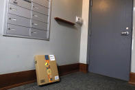 An Amazon package sits by the mailbox at Jason Goldberg's apartment, Monday, March 29, 2021, in Chicago. Amazon is making a push to install a device on buzzer systems in apartment buildings throughout the country that allows its delivery drivers to whip out a phone, tap a button and unlock a building's front doors whenever they need to leave packages in the lobby instead of the street. (AP Photo/Shafkat Anowar)