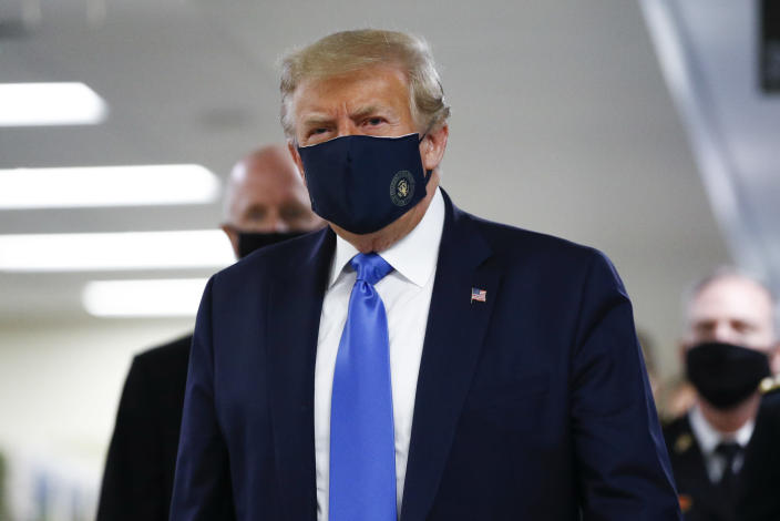 US president Donald Trump wears a mask as he walks down the hallway during his visit to Walter Reed National Military Medical Center in Bethesda, Maryland. (AP)