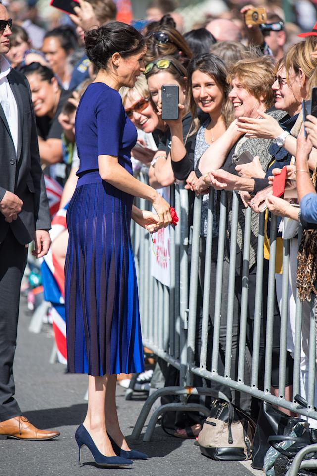 <p>Markle's bespoke pleated Givenchy skirt (approx. $3,283 CAD) is beautiful – but accidentally revealed the duchess's underwear during a walkabout in Royal Springs in Rotorua. The royal paired the look with a navy blue crew neck sweater (approx. $1,500 CAD) and her trusty blue suede pumps. </p>