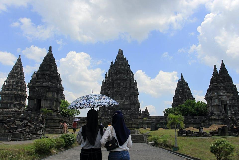 """<span class=""""caption"""">Indonesia has reopened tourism after intensified vaccination campaigns have helped control the spread of COVID-19.</span> <span class=""""attribution""""><a class=""""link rapid-noclick-resp"""" href=""""https://www.gettyimages.com/detail/news-photo/tourists-visit-one-of-the-largest-hindu-temples-in-the-news-photo/1235376076?adppopup=true"""" rel=""""nofollow noopener"""" target=""""_blank"""" data-ylk=""""slk:Feature China/Barcroft Media via Getty Images"""">Feature China/Barcroft Media via Getty Images</a></span>"""