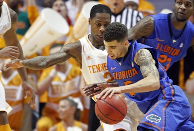 Florida guard Scottie Wilbekin (5) drives against Tennessee guard Antonio Barton (2) in the first half of an NCAA college basketball game on Tuesday, Feb. 11, 2014, in Knoxville, Tenn. (AP Photo/Wade Payne)