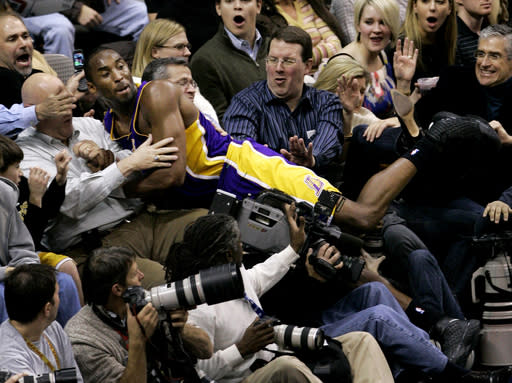 Los Angeles Lakers guard Kobe Bryant lands amongst fans after chasing down a loose ball in the second half of an NBA basketball game against the Dallas Mavericks in Dallas, Friday, Jan. 25, 2008. The Mavericks won 112-105. (AP Photo/Tony Gutierrez)