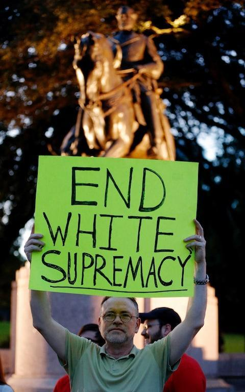 A protester stands in front of a statue of Robert E. Lee - Credit: AP