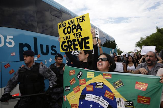 "Protesters hold banners and shout next to the bus carrying some members of Brazil's national soccer team as it departs for the Granja Comary training center, where the team will stay during the World Cup, as riot police try to keep demonstrators away from the bus departing a hotel at the Antonio Carlos Jobim International Airport in Rio de Janeiro, Brazil, Monday, May 26, 2014. Demonstrators protested against the money being spent by the local government on the World Cup. The sign reads in Portuguese ""There will be not Cup. There will be a strike."" (AP Photo/Hassan Ammar)"