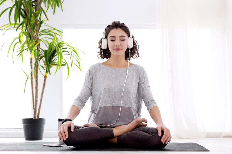 Slender female folded crossed legs in lotus position. Young athletic woman in fitness tracker and headphones is practicing yoga, meditating, relaxing while sitting in padma asana at home.