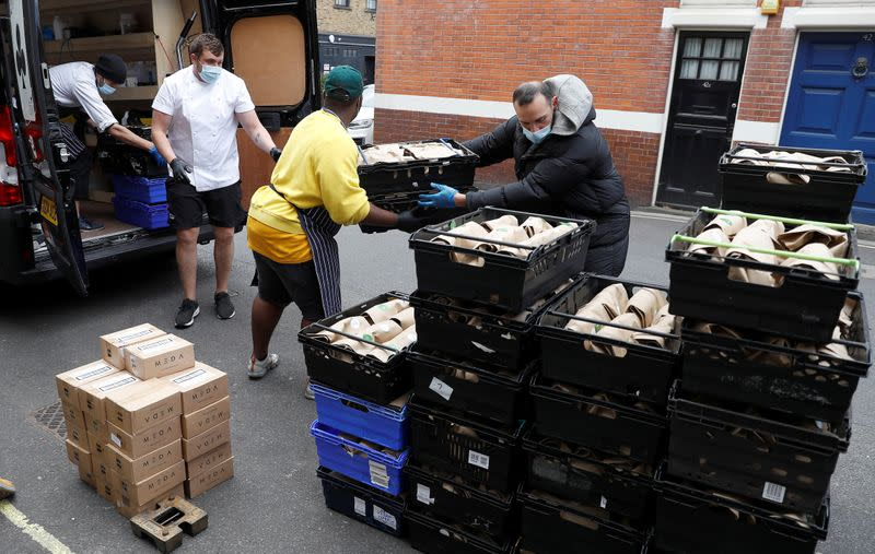 Staff of Annabel's private members club load meals for NHS workers into vans after they were prepared at their premises in London