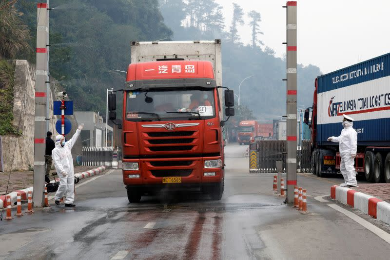 FILE PHOTO: Vietnamese health workers wearing protective suits disinfect a container truck from China at Huu Nghi border gate connecting with China, in Lang Son province