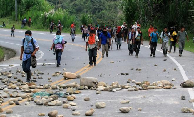 Protesters walk along the Pan-American highway in Piendamo, Cauca, Colombia on Feb. 27, the third day of a coffee farmer strike in the region.