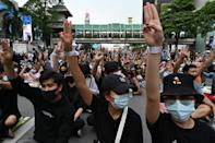 Pro-democracy protesters hold up the three-finger salute during a rally at a traffic intersection in Bangkok on October 15, 2020, after Thailand issued an emergency decree following an anti-government demonstration the previous day. (Photo by Mladen ANTONOV / AFP) (Photo by MLADEN ANTONOV/AFP via Getty Images)