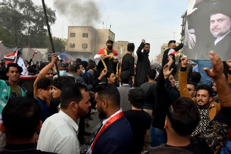 Supporters of Iraqi Shi'ite cleric Moqtada al-Sadr are seen during clashes with anti-government protesters in Nassiriya